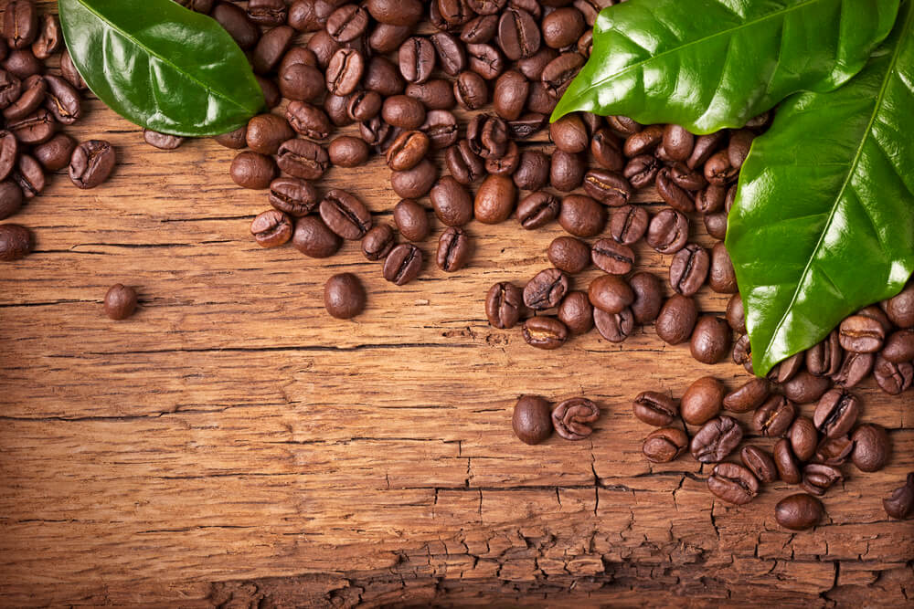 Brown coffee beans are scattered on a wooden table, with three bright green coffee leaves laying on top