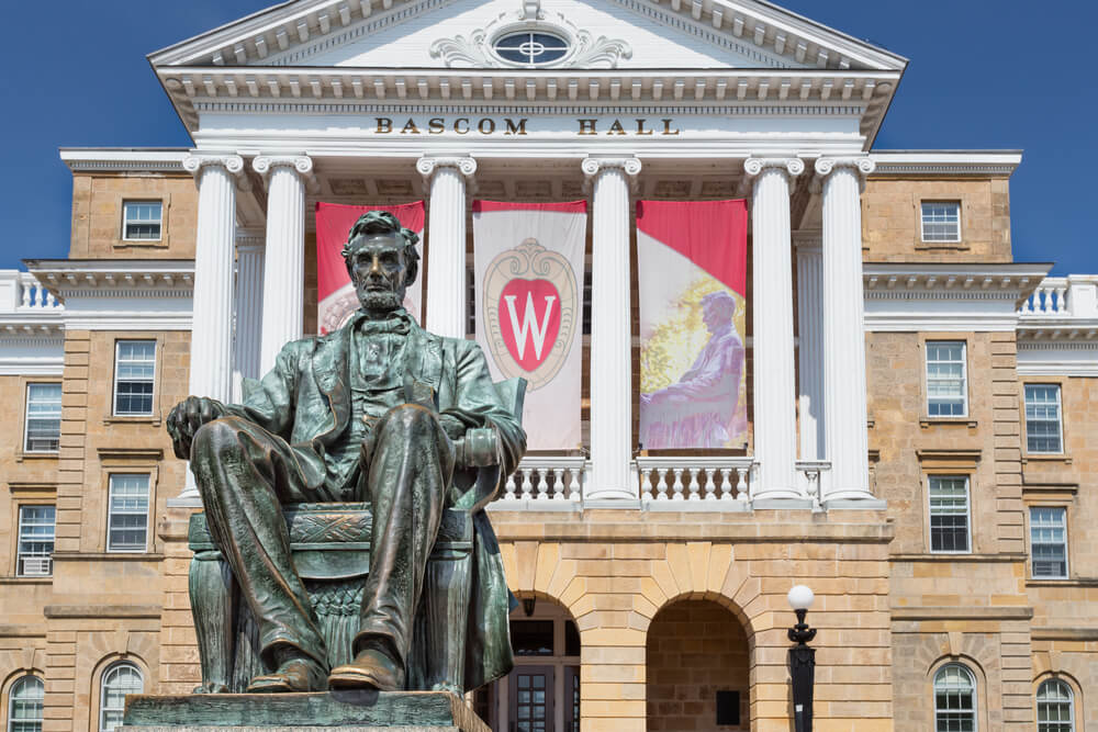 """A bronze statue of Abraham Lincoln sits in front of Bascom Hall. A flag with a big red and white """"W"""" is hanging from the building."""