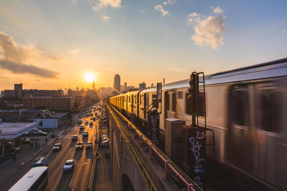 A photo of the NYC subway, blurred because its moving fast. On the left side is a busy street with cars, the sunset is seen in the distance