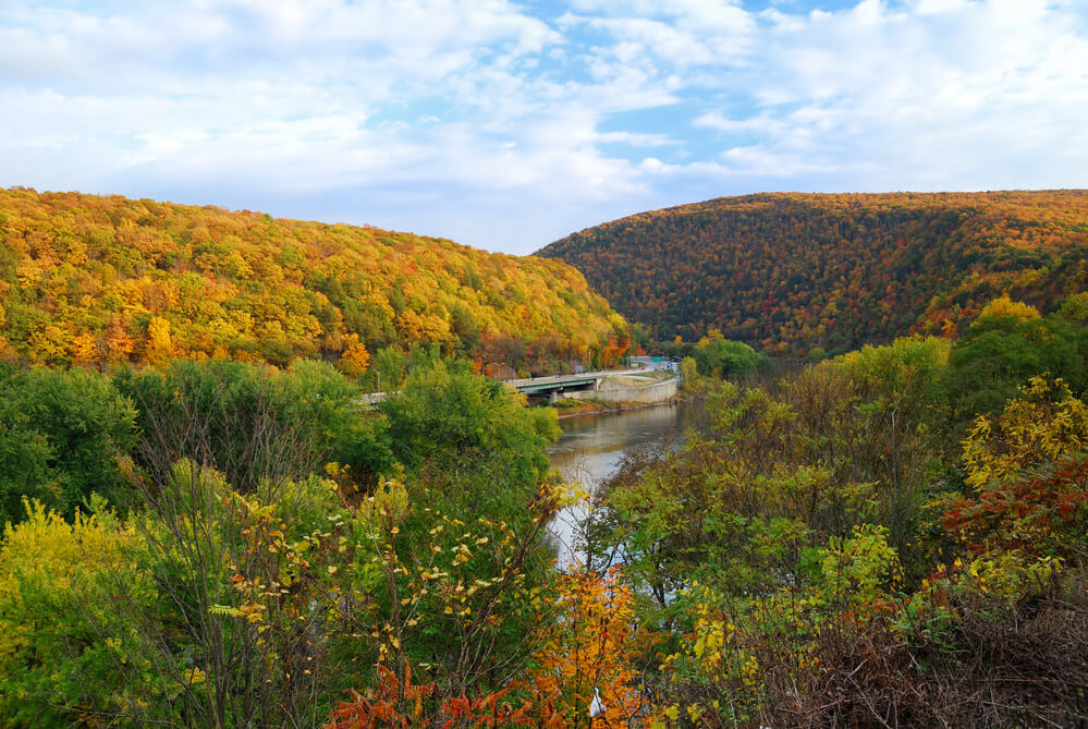 A river cuts through two small mountain hills. The trees are in autumn foliage.