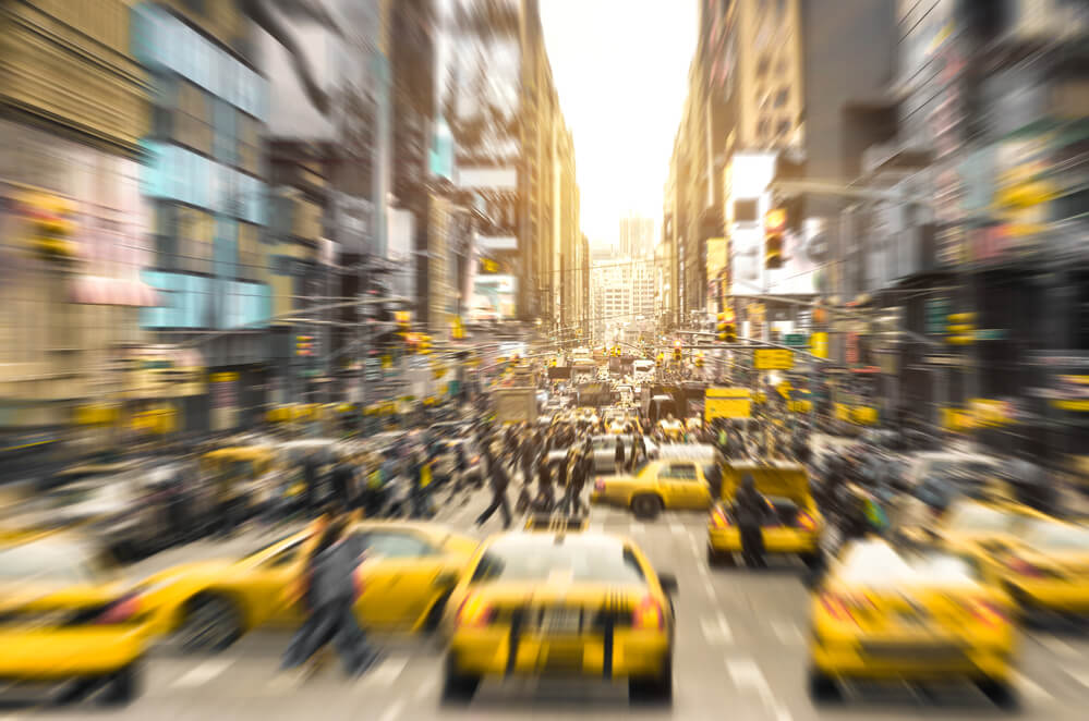 A picture of a very busy NYC street filled with people and taxis. It is blurry to imply movement.