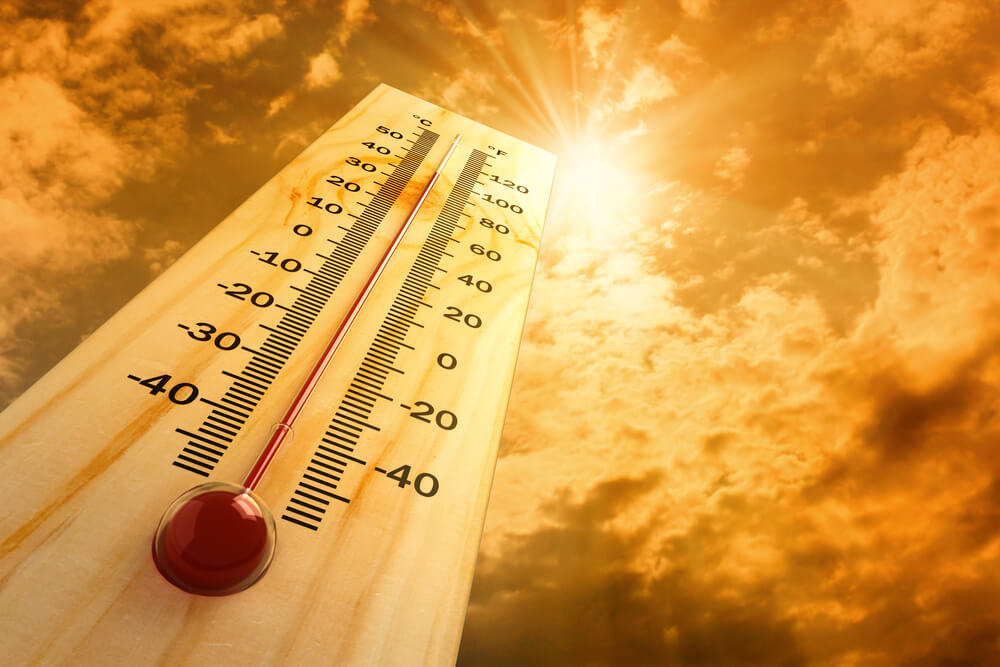 A digital graphic showing a huge thermometer approaching 100 degrees. A red hot sun is seen in the background.