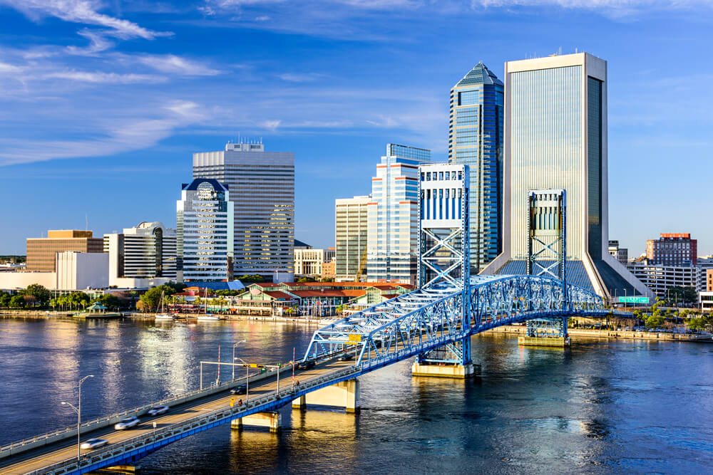 A photo of downtown Jacksonville. There is a river and iron bridge in the front of the picture. Many tall buildings can be seen in the back.