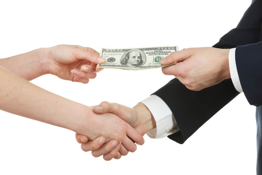 A man in a suit is shaking hands with a woman. They are passing hundred dollar bills with their other hand.