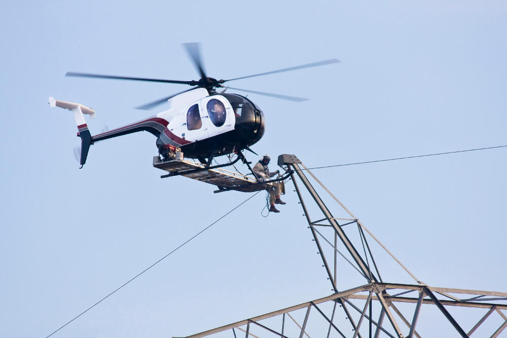 Photo of a helicopter with a man sitting on the outside of the copter. Man appears to be repairing a high voltage power line