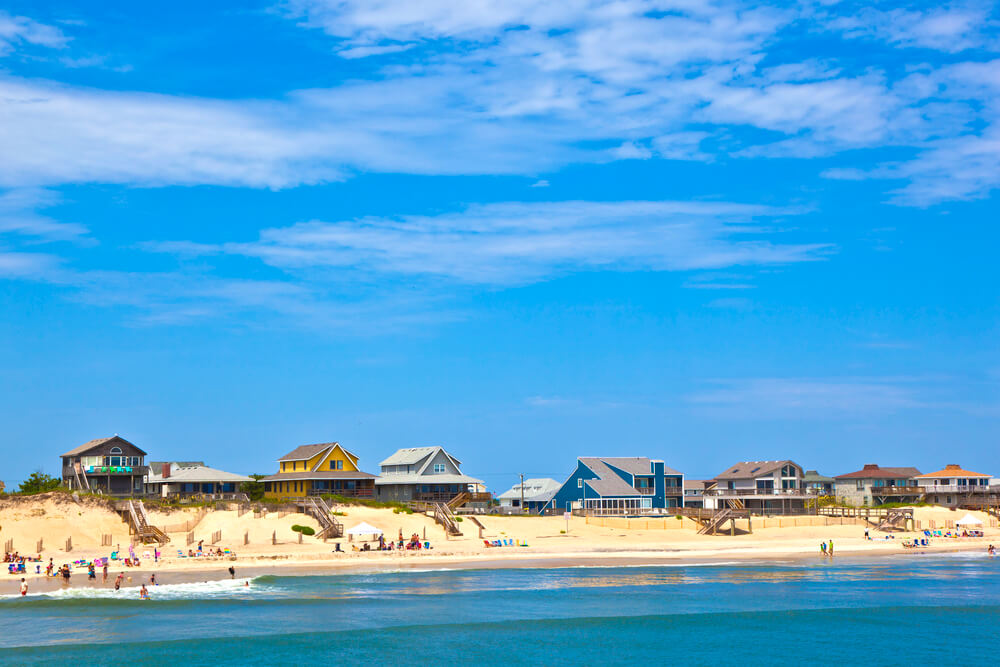 A photo taken from the ocean looking back towards the shoreline. Several brightly colored beach houses can be seen. There are people on the beach