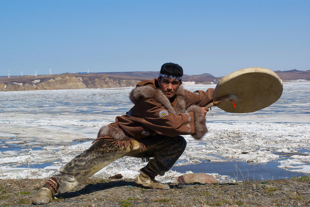 A native person, dressed in traditional seal leather, is playing a drum. There is icy water in the background.
