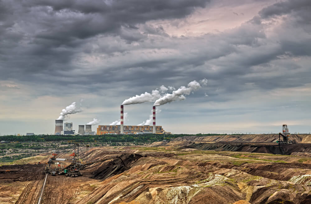 A photo of ugly strip mining in the front, an ugly smoking plant in the back, dark grey skies above