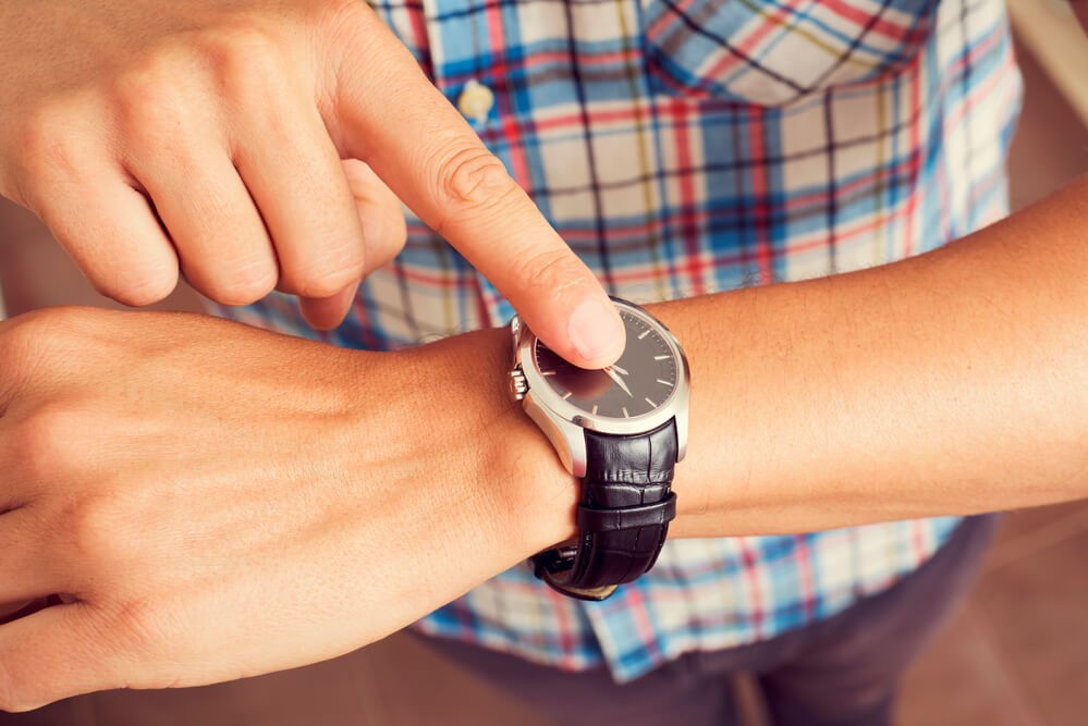 """A close-up of a man's arm. He has on a black watch. The man is pointing at the watch as if to say """"time is wasting"""""""