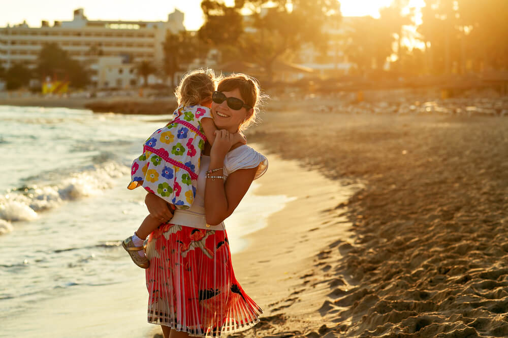 A woman holds a young child while standing on a beach, the sun is setting in the background