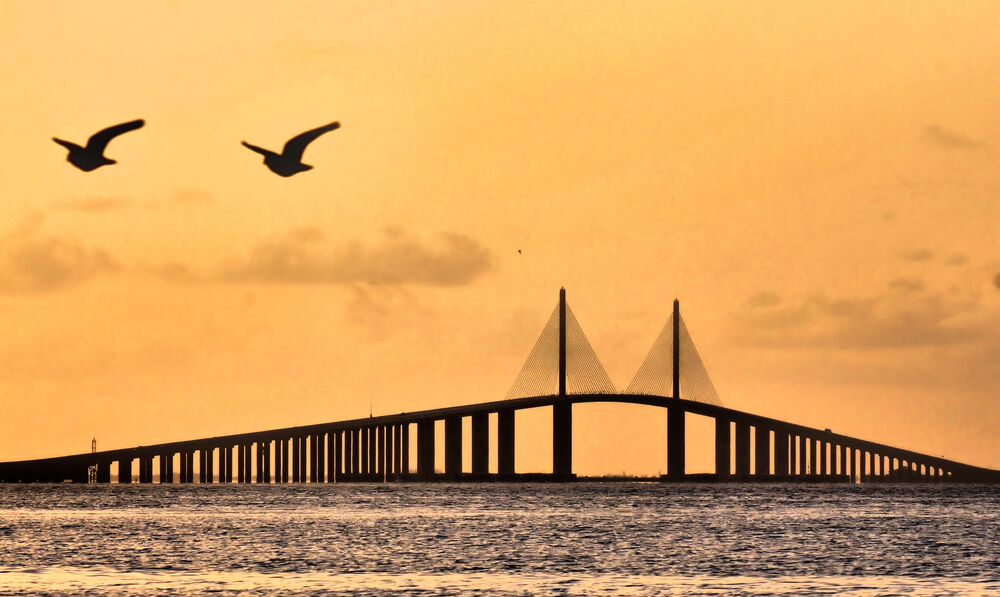 A photo of a sunset over Tampa Bay. A large bridge is at the center of the photo. Orange skies in the back, calm waters in front.