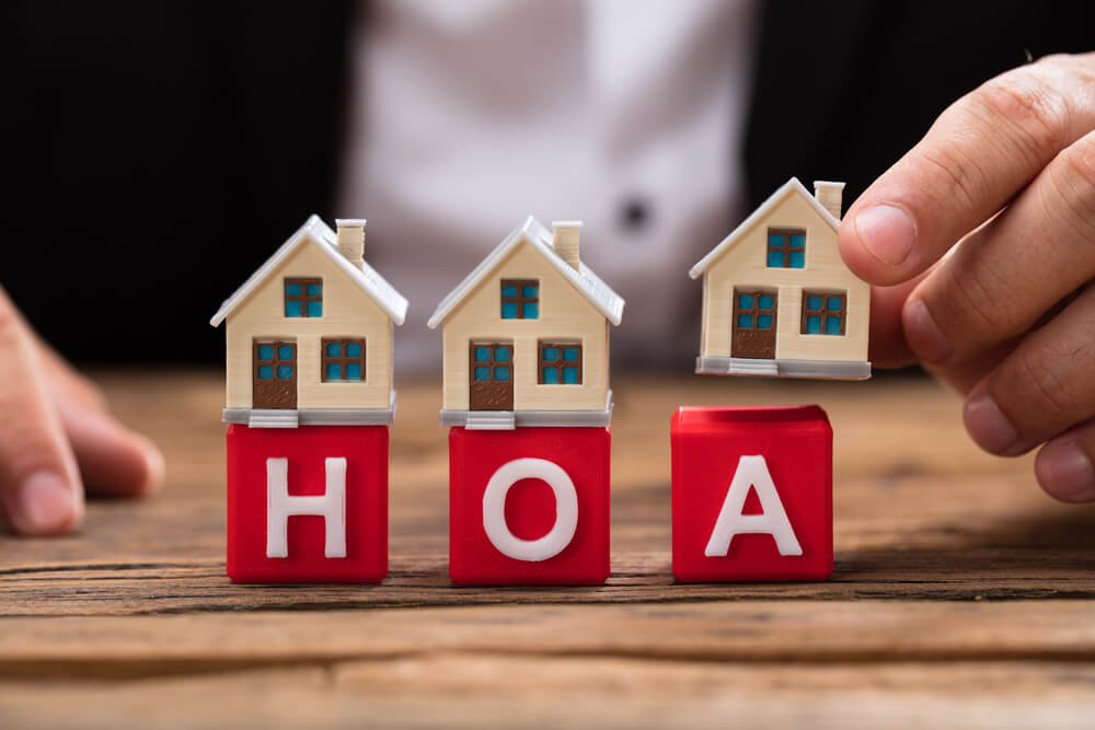 There are 3 red blocks sitting on a wooden table. They spell HOA. A man's had is seen, placing a little wooden house on top of the blocks.
