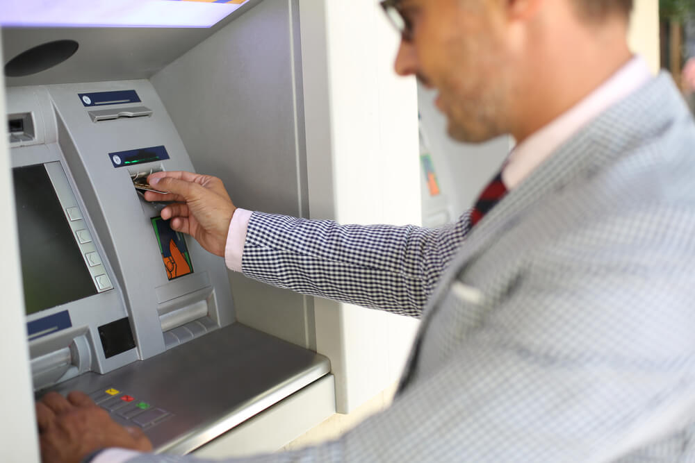 A man in a suit is inserting a debit card into the ATM. He is looking at the screen, getting ready to hit buttons.