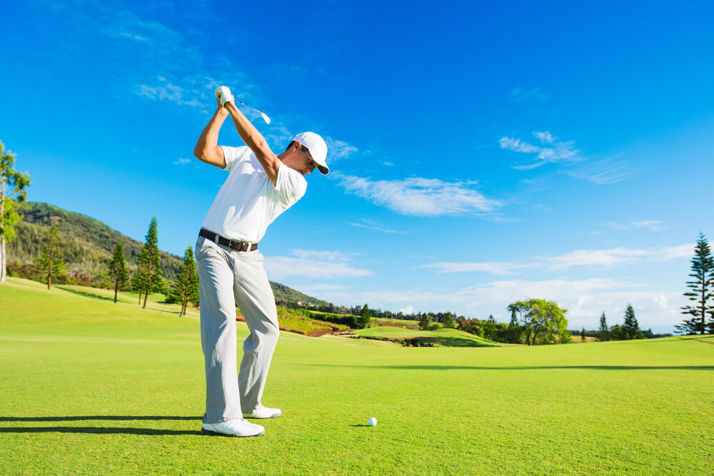 A man is playing golf. Dressed in all white, he is swinging his club. Green trees and green grass can be seen.