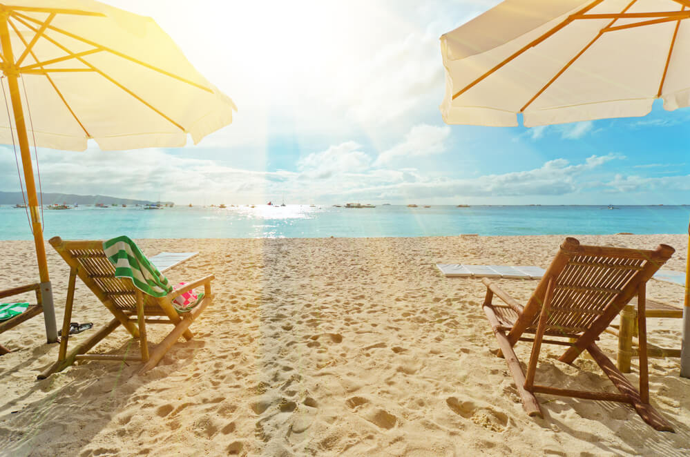 A photo of two beach chairs sitting on white sand, overlooking emerald green waters, with a bright sun shining into the lens