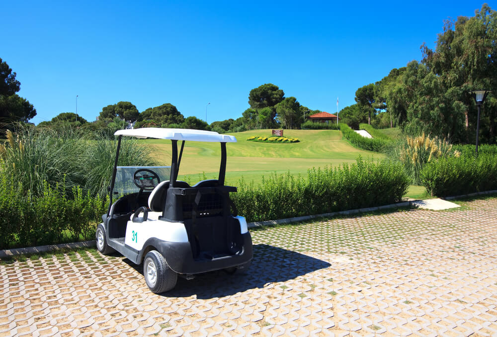A photo of a white golf cart. It is parked on a brick walkway. Towards the back is the lush rolling green of a golf course.