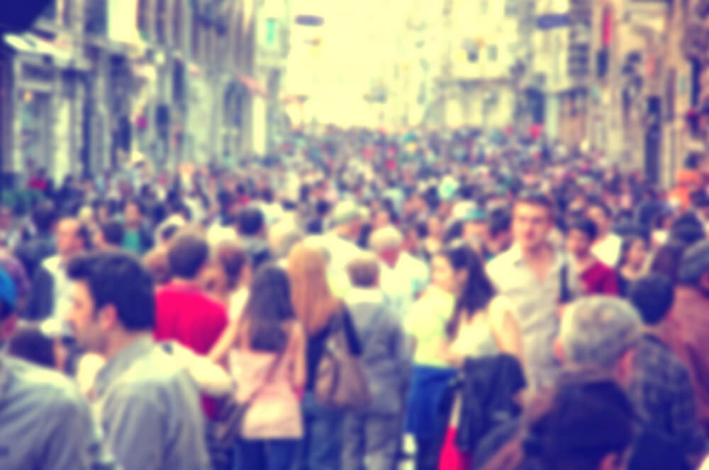 A blurry photo of a very crowded street full of people walking