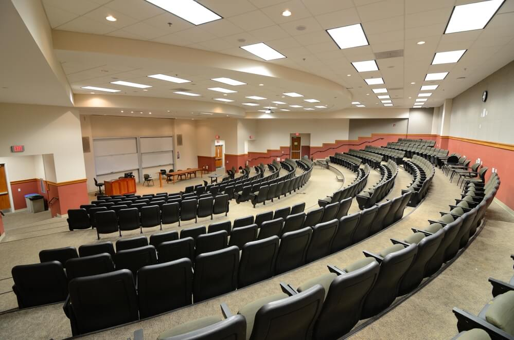 A photo of a university lecture hall. Rows of black chairs circle a lecture stand