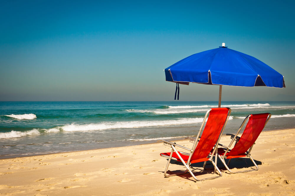 A photo of a orange beach chairs sitting on white sand, over-looking emerald green waters